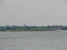 Widoczny przy zaporze włocławskiej krzyż postawiony na pamiątkę wizyty Jana Pawła II oraz miejsce wrzucenia do Wisły ciała księdza Jerzego Popiełuszki. Zdjęcie od strony wody poniżej stopnia wodnego Włocławek.