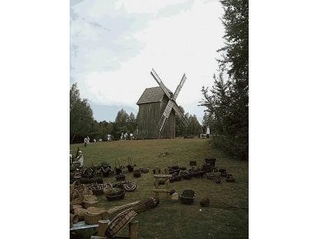 Na dalszym planie widoczny wiatrak, na bliższym wyroby ludowego rzemiosła - plecione koszyki