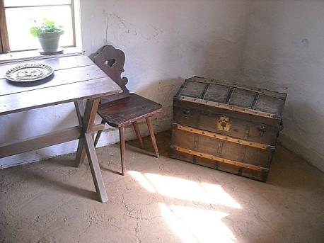 Drewniany stół, krzesło i tajemniczy kufer - izba z końca XVIII wieku