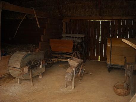 Wnętrze szopy na terenie najstarszego gospodarstwa, widać stare wozy i maszyny rolnicze