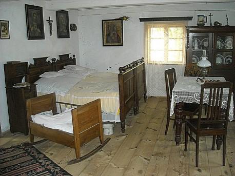 Wnętrze chałupy - izba mieszkalna: łóżko, kołyska, krzesła, obrazy